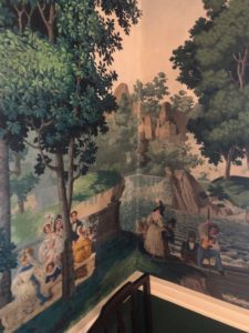 Corner of Gracie Mansion dining room that focuses on Zuber wallpaper. Young couple move through a park.