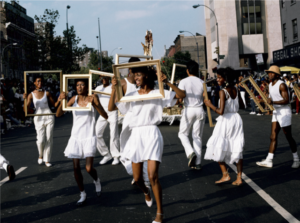fifteen African-American and Latino performers dressed in white and holding empty gold picture frames