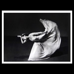 Done in black and white photography a young woman in a white draping dres angles her torso and head parelle to the floor as she kicks her left leg backward.